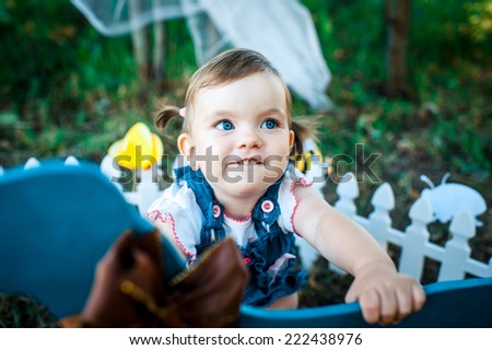 cute baby-girl  playing with a dog toy in park - stock photo