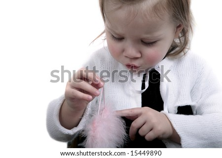 Cute baby girl playing with angel wings - stock photo