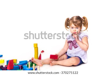 Cute baby girl playing with building blocks isolated on white