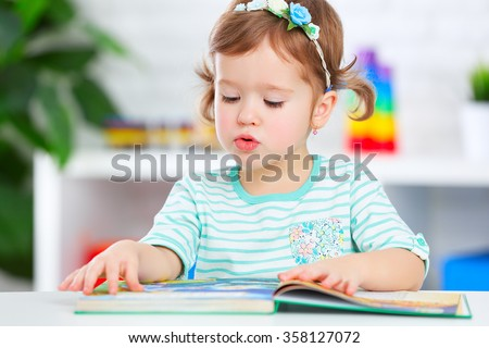 cute baby girl reading a book at home  - stock photo