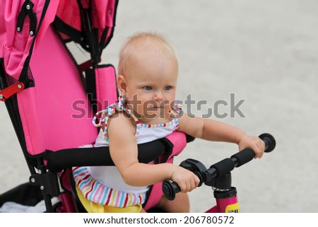 Cute baby girl riding her first bicycle  - stock photo
