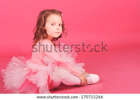 Cute baby girl sitting on the floor wearing pink dress at pink background in studio