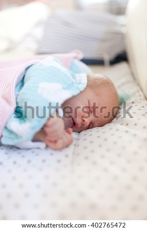 Cute baby girl sleeping on sofa covered with blanket and diaper.
