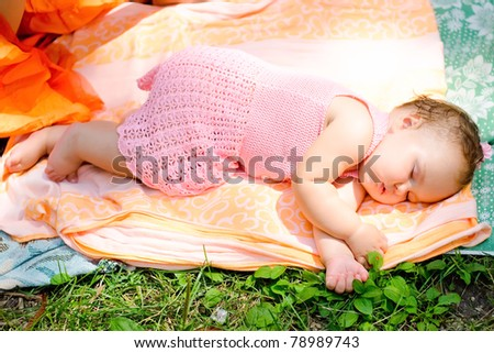 Cute baby girl sleeping with her hands under her face in the open air