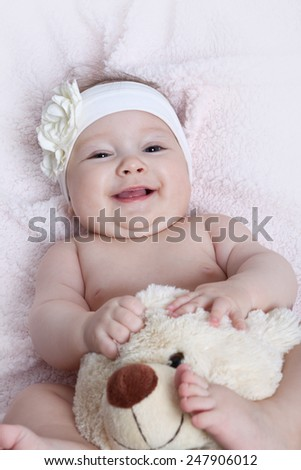Cute baby girl smiling and playing with teddy bead - stock photo