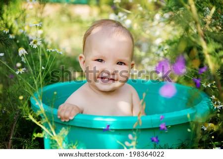 cute baby girl taking water procedures in summer garden - stock photo