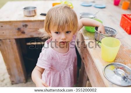 Cute baby girl toddler in pink dress playing with toy kitchen outdoors - stock photo