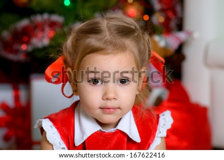 Cute baby girl  under christmas tree indoors looking right in the camera
