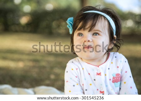 cute baby girl with a watchful eye in the park