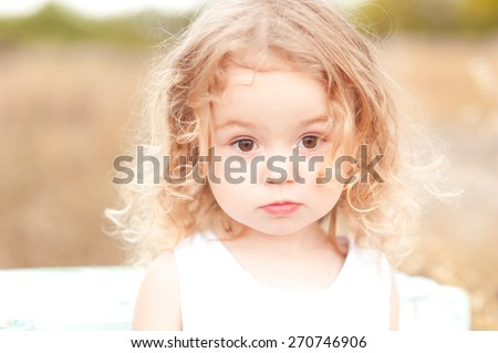 Cute baby girl with blonde curly hair outdoors. Little girl 2-3 year old.  - stock photo
