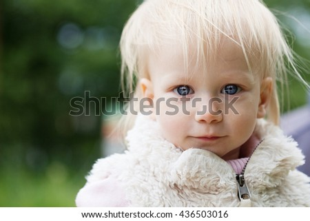 Cute baby girl with blonde hair outdoors. Little girl 1-2 year old, close-up - stock photo