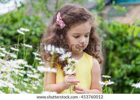 Cute baby girl with daisy flowers outdoors - stock photo