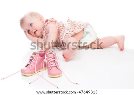 cute baby girl with pink shoes.she is wearing pink dress - stock photo