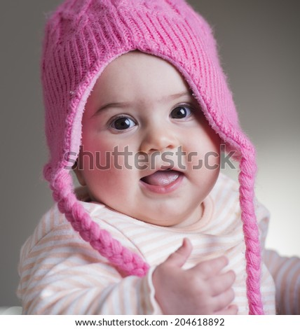 cute baby girl with pink woolen hat smiling - stock photo