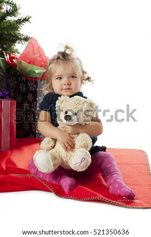Cute baby girl with teddy bear dressed at a Christmas tree festive background against a white background