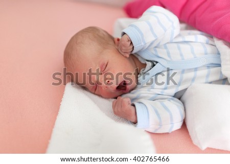 Cute baby girl yawning in bed.