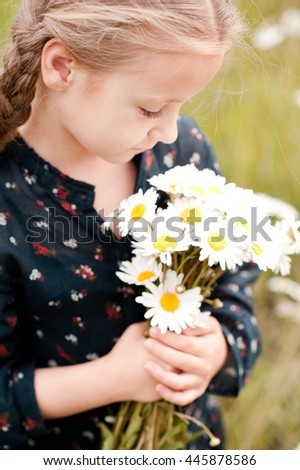 Cute baby girl 3-4 year old holding camomiles outdoors. Top view. Childhood. Summer portrait.  - stock photo