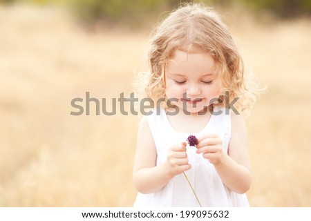 Cute baby girl 2-3 year old holding flower in meadow outdoors. Childhood.  - stock photo