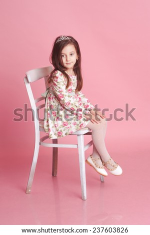 Cute baby girl 4-5 year old sitting on white chair over pink in room. Wearing floral pattern dress