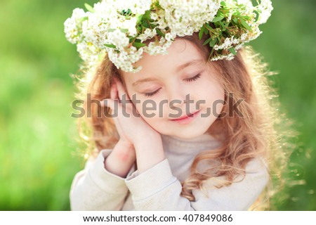 Cute baby girl 3-4 year old wearing flower wreath over green nature background. Posing outdoors. Childhood. Spring season.  - stock photo