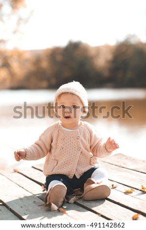 Cute baby girl 1 year old wearing stylish knitted clothes posing in autumn park outdoors. Looking at camera.