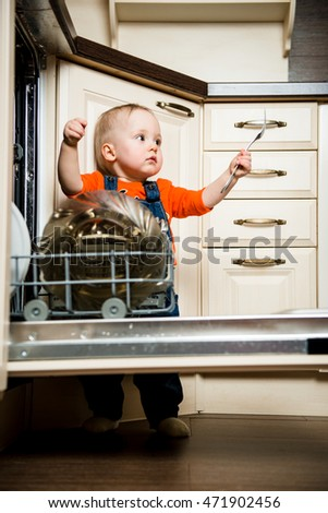 Cute baby helping mother unload dishwasher in kitchen