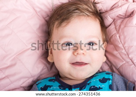 Cute baby in a pink bed. Portrait of a baby.Portrait of a smiling child. A child on a white bed. Handsome boy.