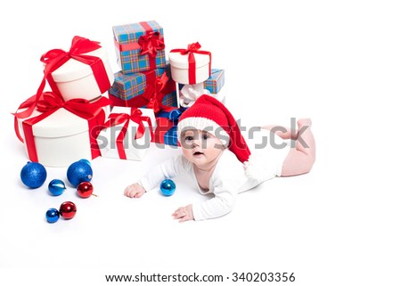 Cute baby in a red New Year's cap with a smile on his face lying on his stomach on a white background surrounded by boxes with gifts, and blue and red Christmas balls