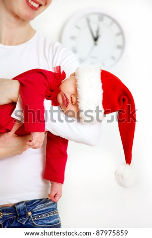 Cute baby in Santa hat sleeping in mothers hands - stock photo