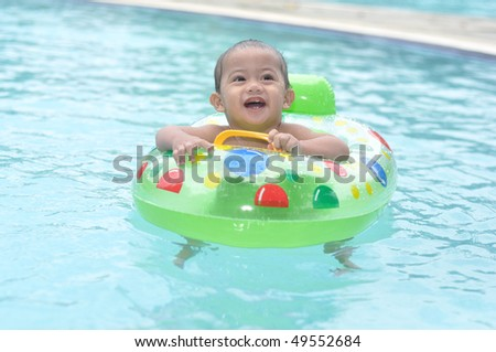 cute baby in swimming pool - stock photo