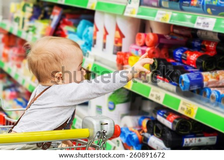 Cute baby in the supermarket trolley is reaching to shop stuff in household goods department  - stock photo