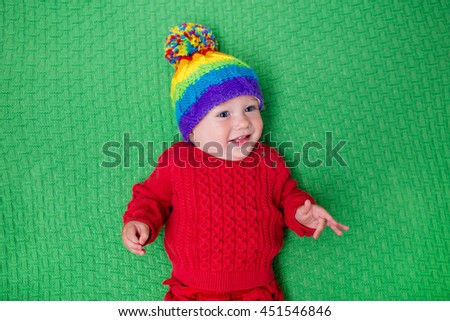 Cute baby in warm wool knitted hat on a red blanket. Autumn and winter clothing for young kids. Colorful knitwear for children. Adorable little boy ready for a walk on a cold fall day. - stock photo
