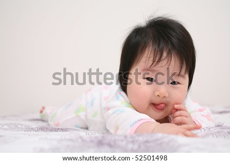 Cute Baby Infant Asian Girl with Tongue Sticking Out