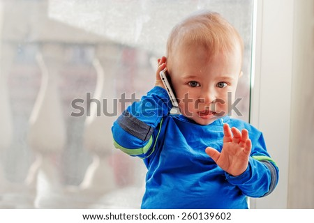Cute baby is playing with mobile phone as he is calling to somebody - stock photo