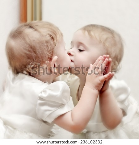 Cute Baby Kissing a oneself Reflection in the Mirror - stock photo