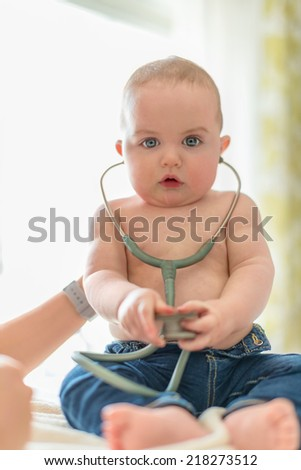 Cute baby listening to a stethoscope - stock photo