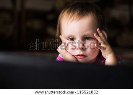 Cute baby looking thoughtfully into the laptop. - stock photo