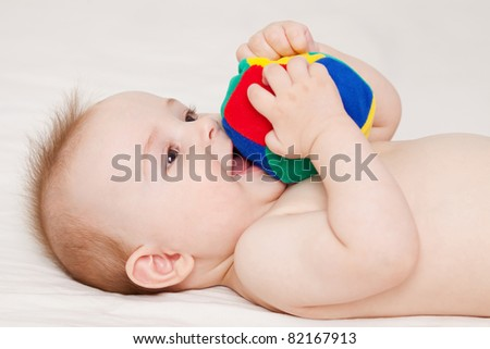 Cute baby lying and playing with a ball - stock photo