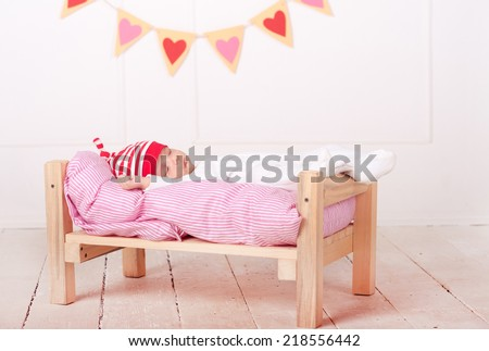 Cute baby lying in bed with valentines hearts on background - stock photo