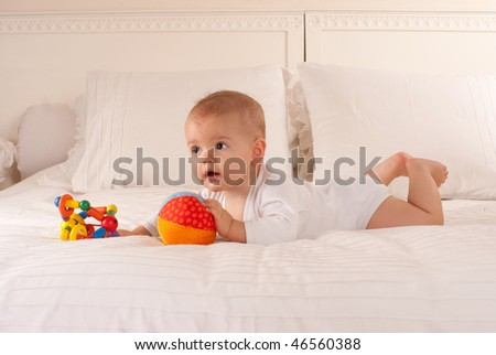 Cute baby lying on a bed holding a colourful toy and a soft ball - stock photo