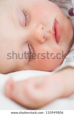 Cute baby lying on a bed while sleeping in a bright room - stock photo