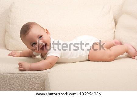 Cute baby lying on a sofa - stock photo