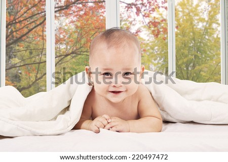 Cute baby lying on bedroom and smiling at camera with autumn tree background - stock photo
