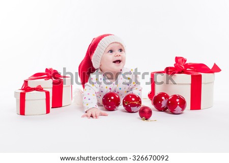 Cute baby lying on his stomach in a New Year's cap among Christmas balls and red box with presents and looking at the camera with a smile on his face, picture with depth of field - stock photo