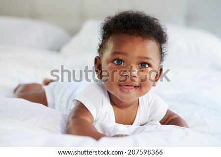 Cute Baby Lying On Tummy In Parent's Bed - stock photo