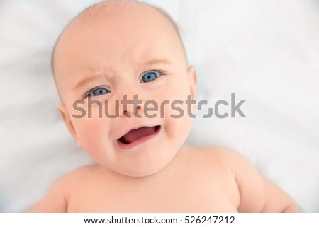 Cute baby lying on white bed sheet, close up view