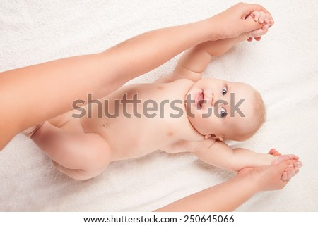 Cute baby lying on white blanket on back, hands lifted. Isolated over white background. - stock photo