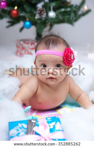 Cute baby near Christmas tree at home