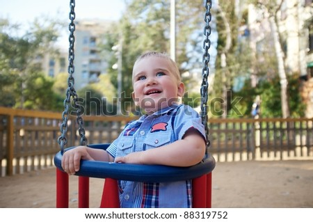 Cute baby on a swing in a park - stock photo