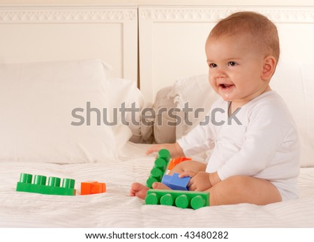 Cute baby on a white bed playing with colourful toy brick - stock photo